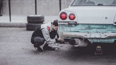 Man changing tire on a old car