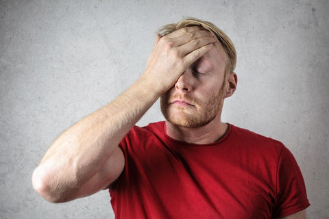 Man holding his hand over his forehead with eyes closed.