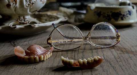 Dentures sitting out on table with glasses behind them