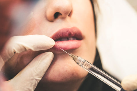 Women recieving a botox injection in lower lip