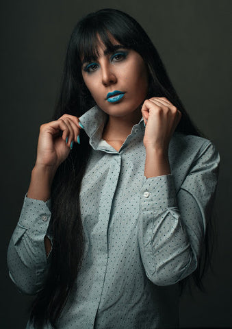 brunette girl wearing shirt with blue lipstick and nail polish