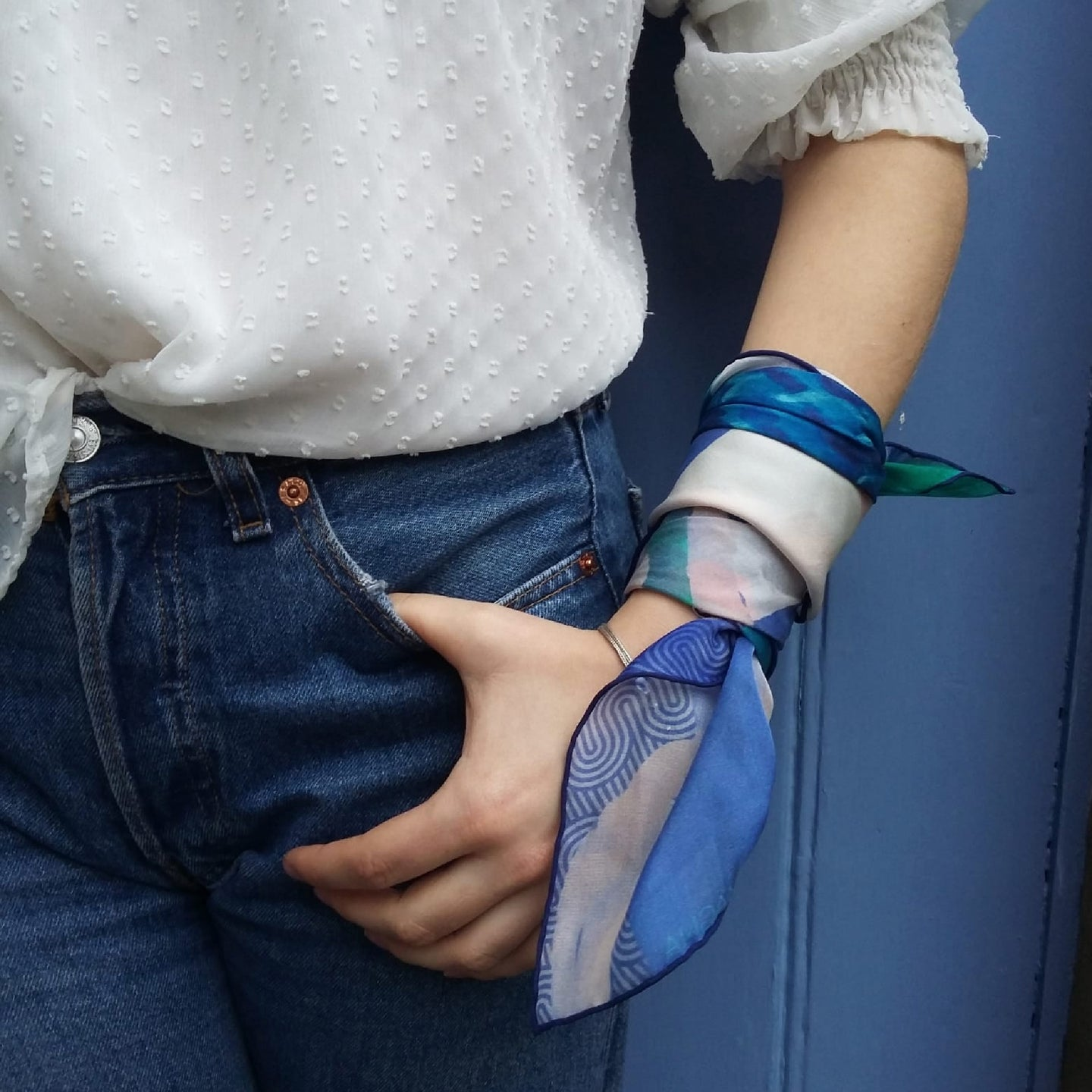 blue silk chiffon scarf tied around wrist