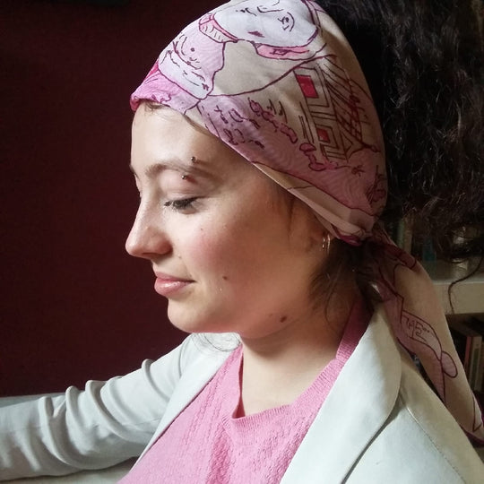 girl wearing pink chiffon scarf around head