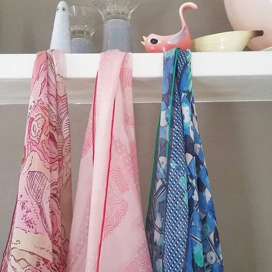 three silk chiffon scarves hanging from a shelf