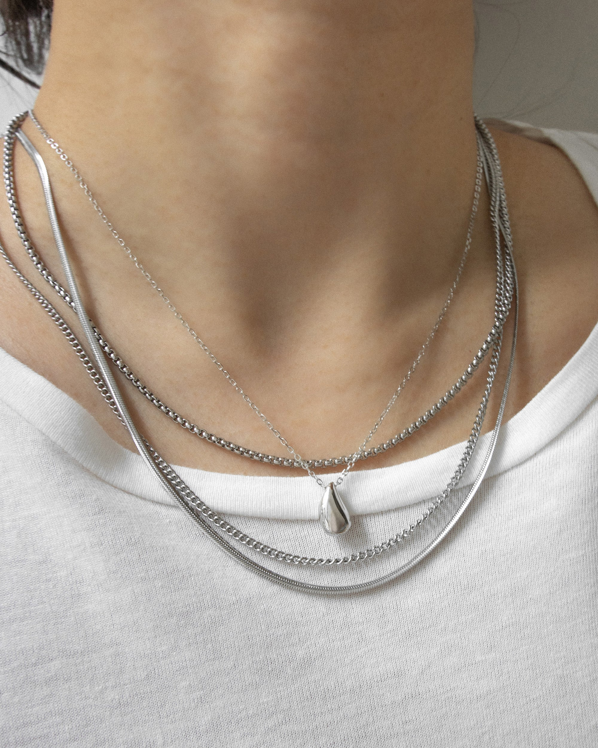 Silver teardrop pendant necklace anchors the neck stack for a cohesive look