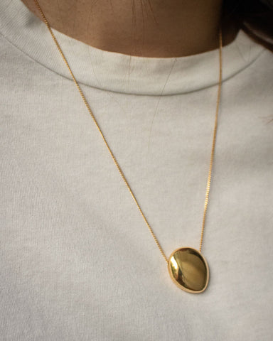 A timeless looking necklace featuring a smooth round pebble-like pendant - The Hexad Jewelry