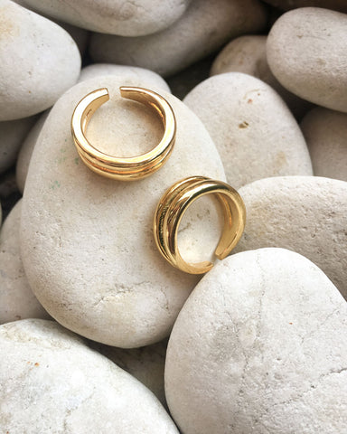Close up of trendy gold rings set against smooth pebbles - The Hexad