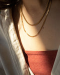 Gold necklace stack with The Hexad's Woven Chain and Cuba Chain