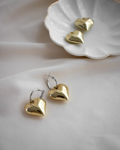 Cute chubby golden heart earrings hanging from a silver hoop - The Hexad
