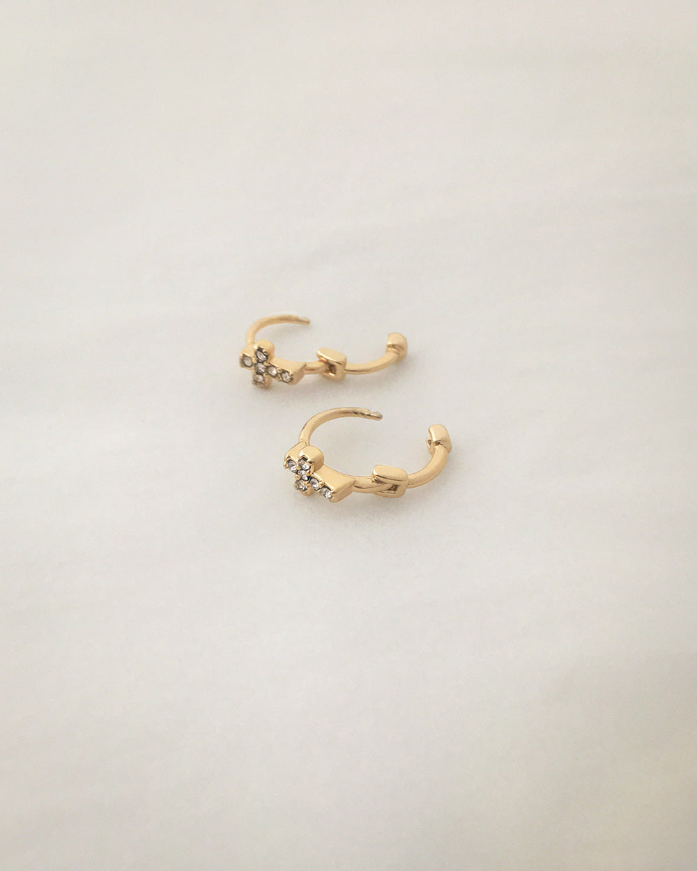 Dainty huggie hoops featuring a tiny gold cross - The Hexad Jewelry