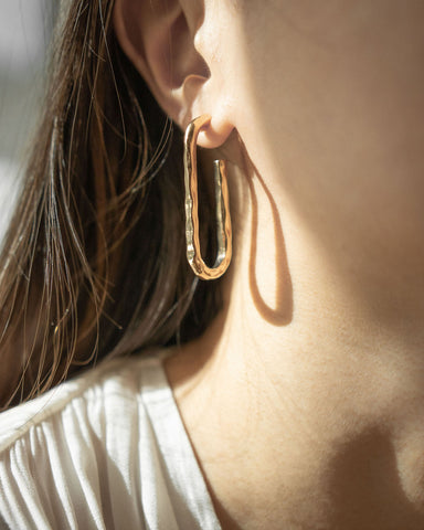 Elongated hammered hoop earrings in gold by The Hexad