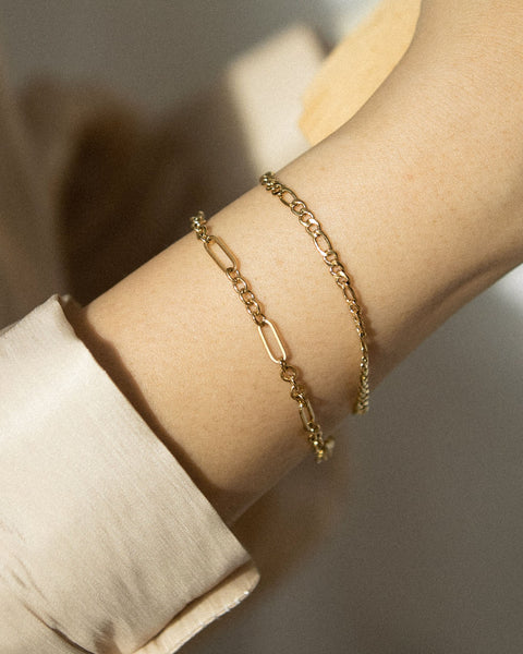 Figaro and oval chain link style bracelets in gold. by The Hexad