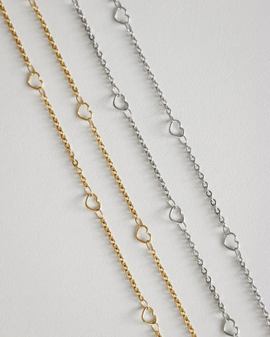 Gold and silver chain necklaces strung with mini hearts - The Hexad