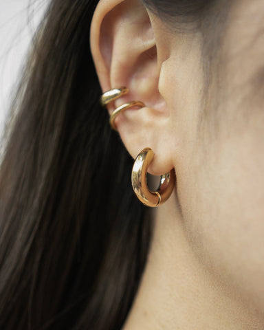 Golden ear stack featuring bold huggie hoops and minimalist ear cuffs
