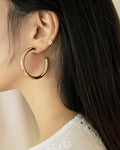 Thick tubular gold hoop earrings by The Hexad