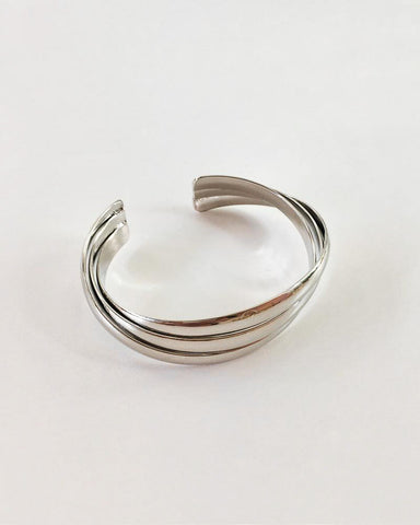 Three silver cuffs intertwined and twisted to make a unique statement bangle - TheHexad