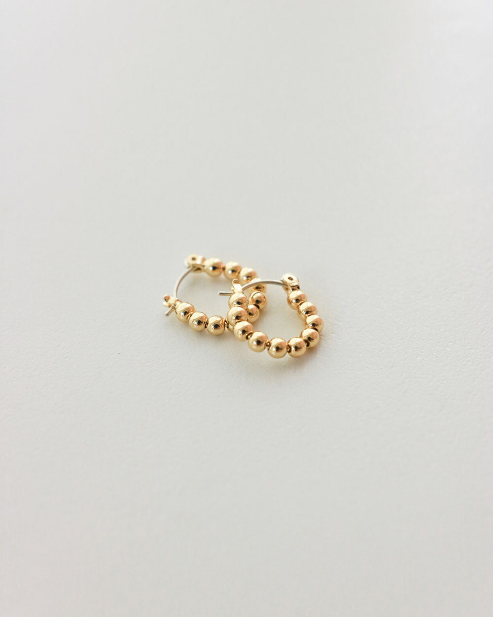 Tiny gold spheres earrings by The Hexad