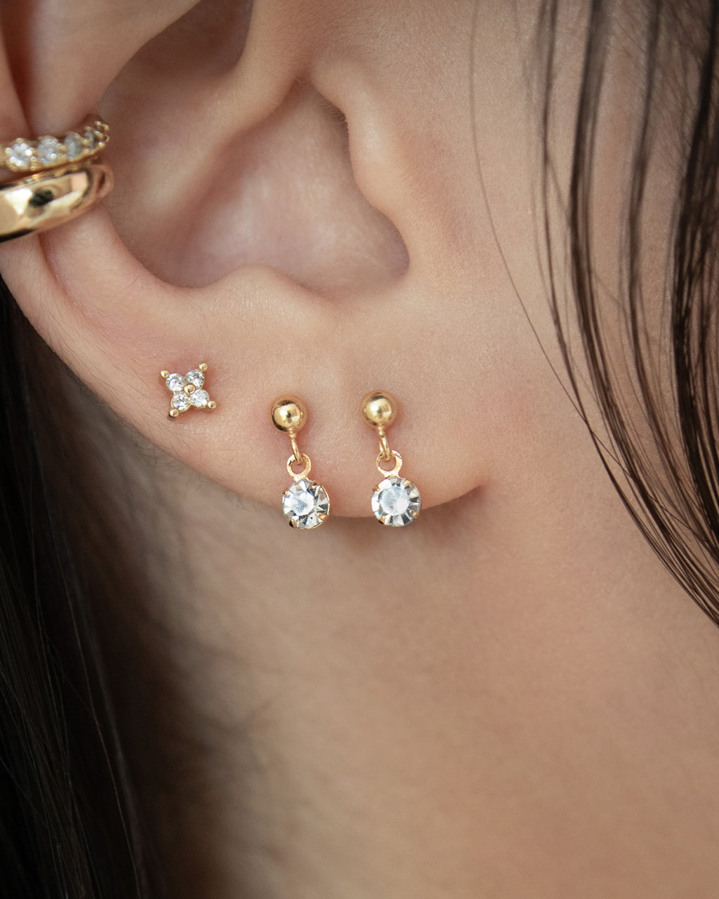 chic charm earrings layered with ear cuffs by jewelry label the hexad
