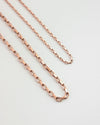 close up detailing of the parallel chain necklaces in rold gold hue from the hexad