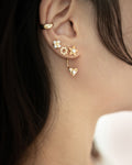 cult ear cuff layered with multiple stud earrings for dream stack inspiration