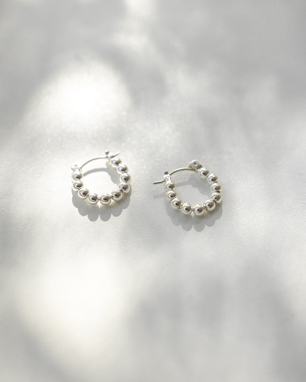 Minimalist silver hoop earrings with tiny spheres by The Hexad