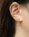 modern gold ear stack with drop chain earrings by the hexad