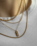 multiple gold chain necklaces layered together against a simple white tee @thehexad