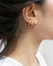multiple piercings look styled with uki huggie earrings in rose gold from the hexad