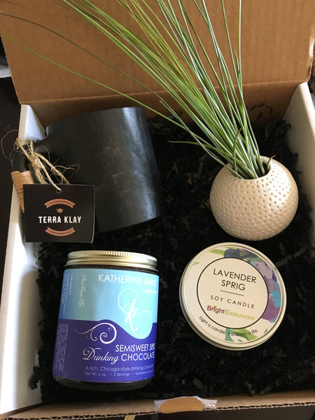 Curated Gift box for any occasion with handmade black clay mug and candle, drinking cocoa, and pot with planter
