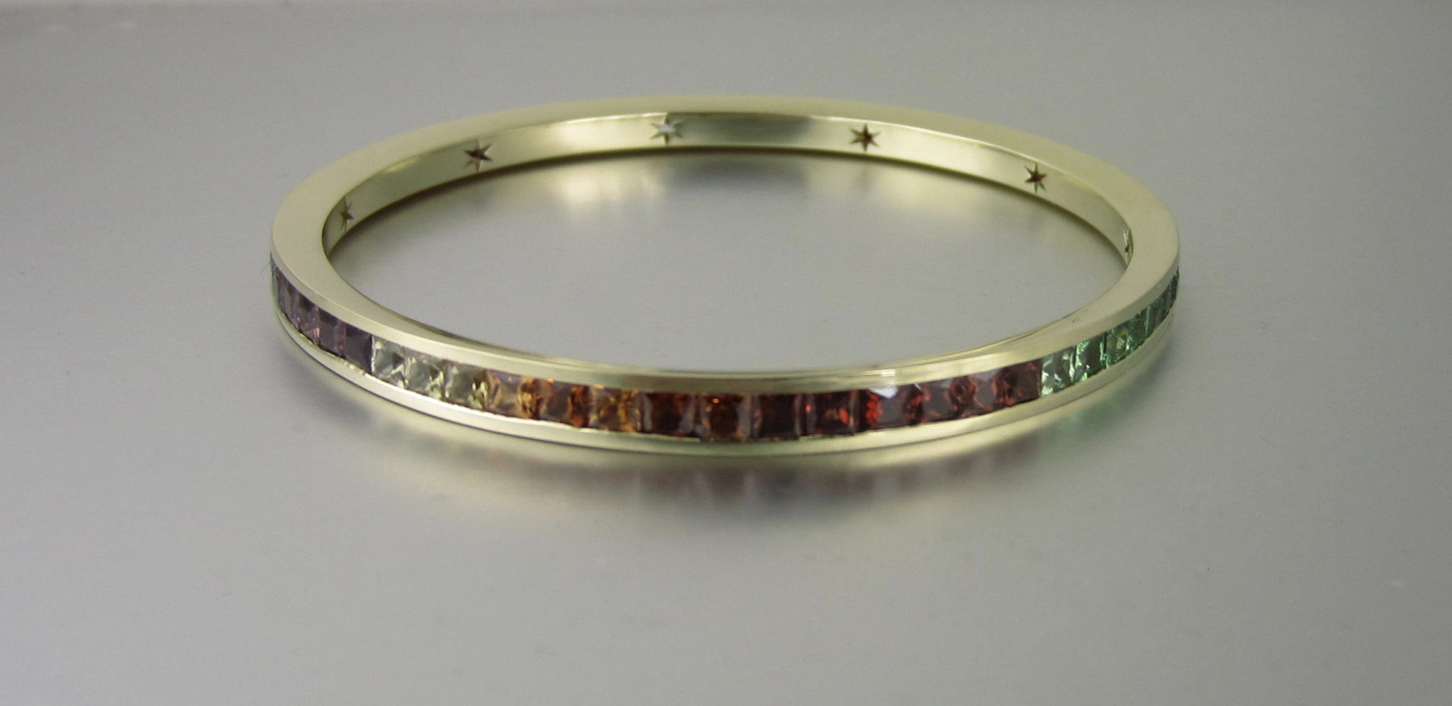 Rainbow Garnet bangle in 18ct yellow gold.