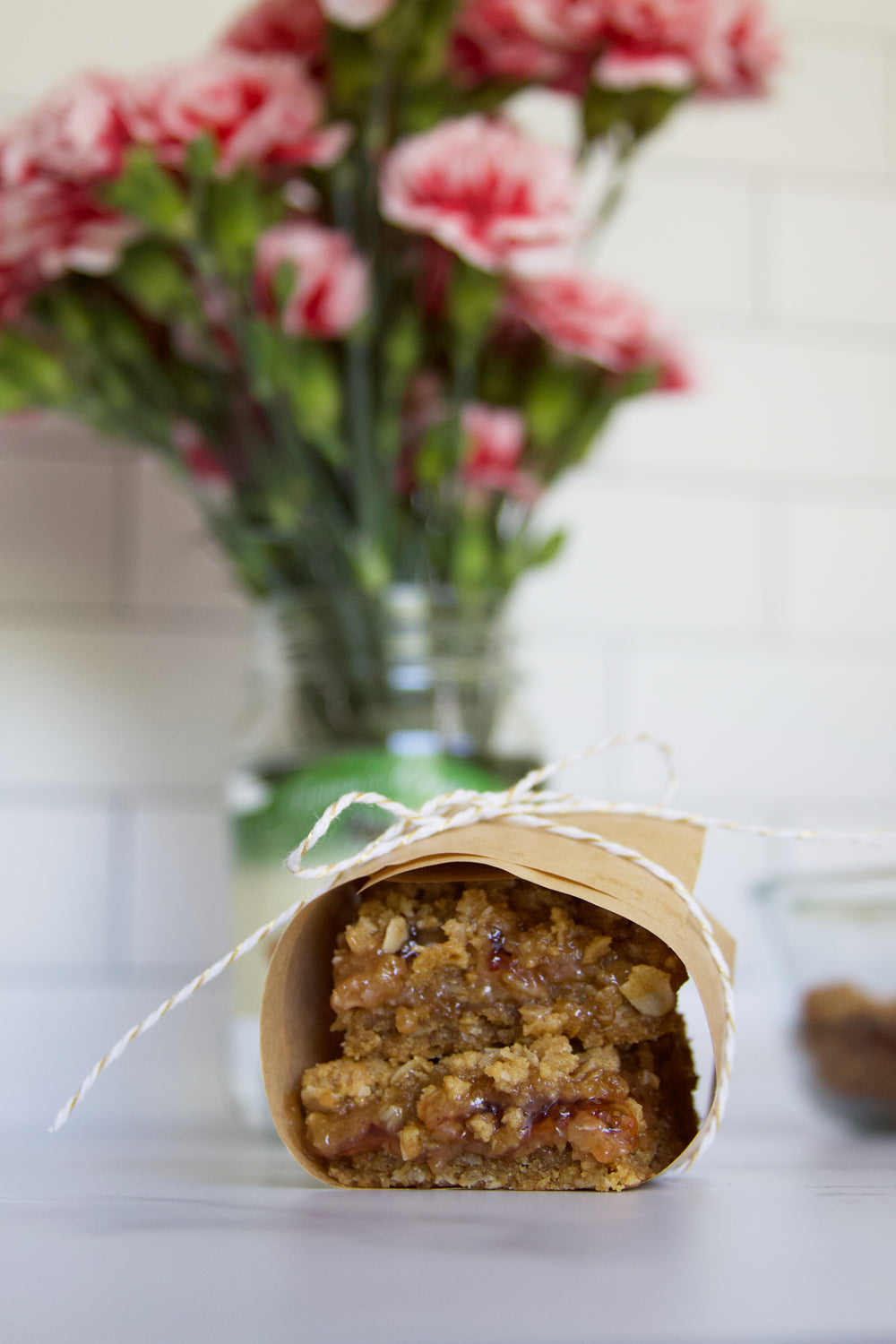 Peanut butter and jelly bars wrapped in paper with pink carnations in a Raven's Nest jar