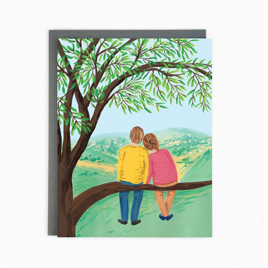Couple in a tree looking at the hills