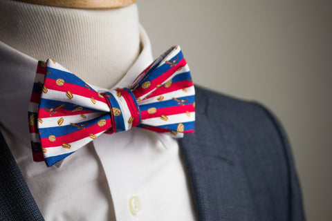 An american flag bow tie with a suit facing foward