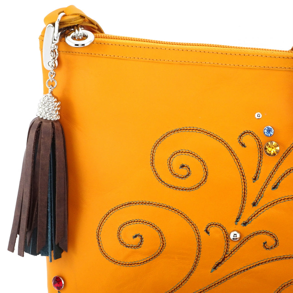 Rosie Mustard leather stitched swirl details small tote bag showing tassel