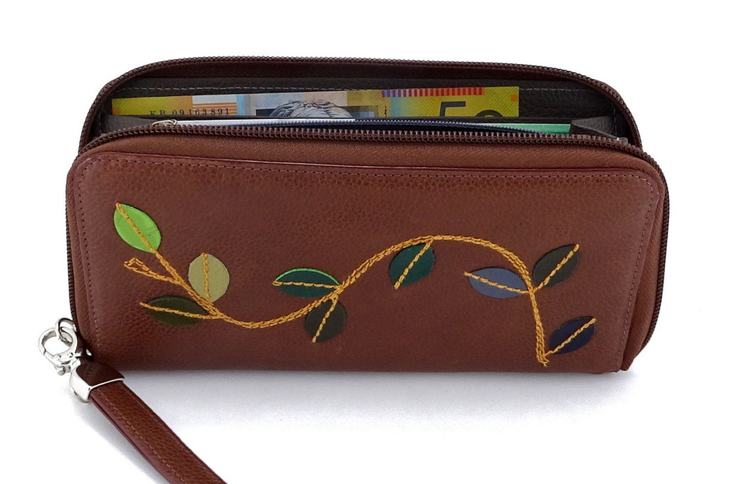 Victoria  Mid brown leather vine detail ladies zip around purse side view showing money note