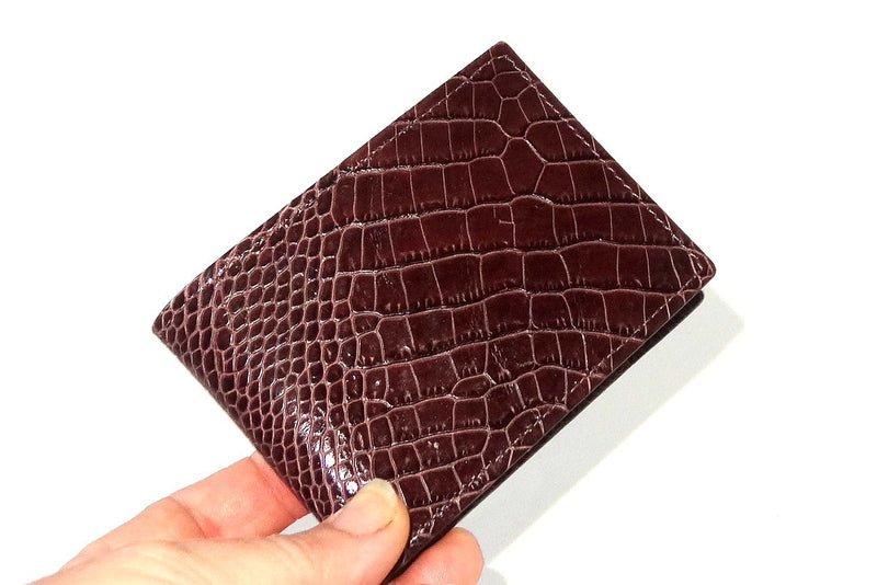 hand with Burgundy printed leather small men's wallet held in hand