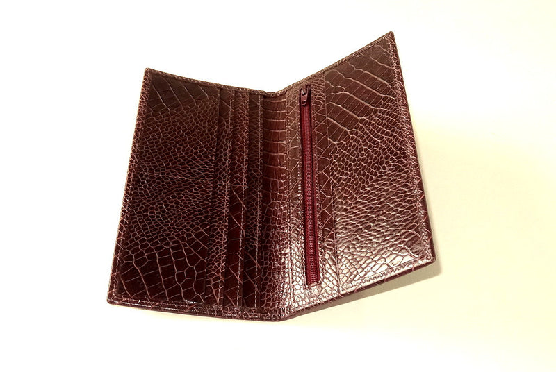Inside view of suit wallet made in crocodile printed burgundy brown leather cards on left side and zip section right side