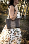 Emily  Medium leather tote bag in a grey crocodile print showen on model