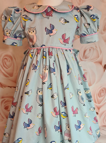 Girls party dress with pink piping and puff sleeves