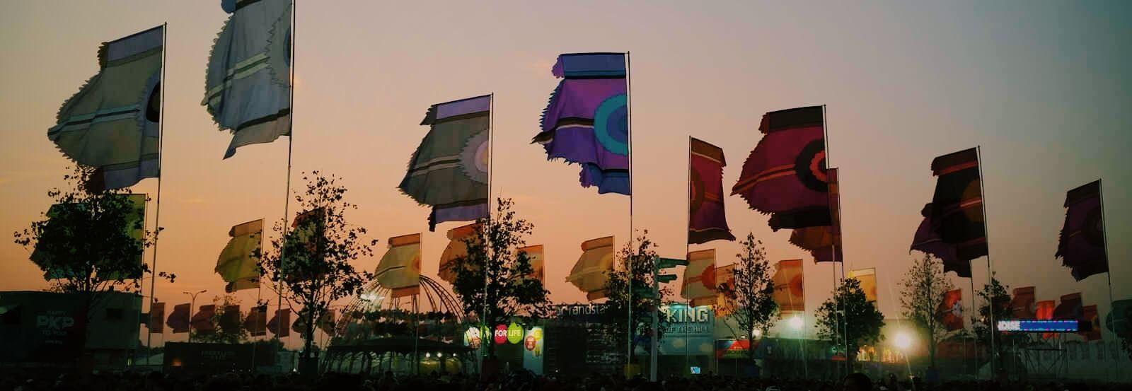 Music festival scene with flags and sunset