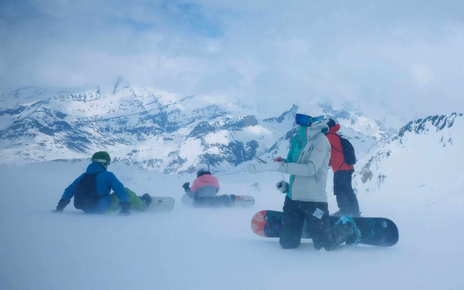 Snowboarders in fog and wind at top