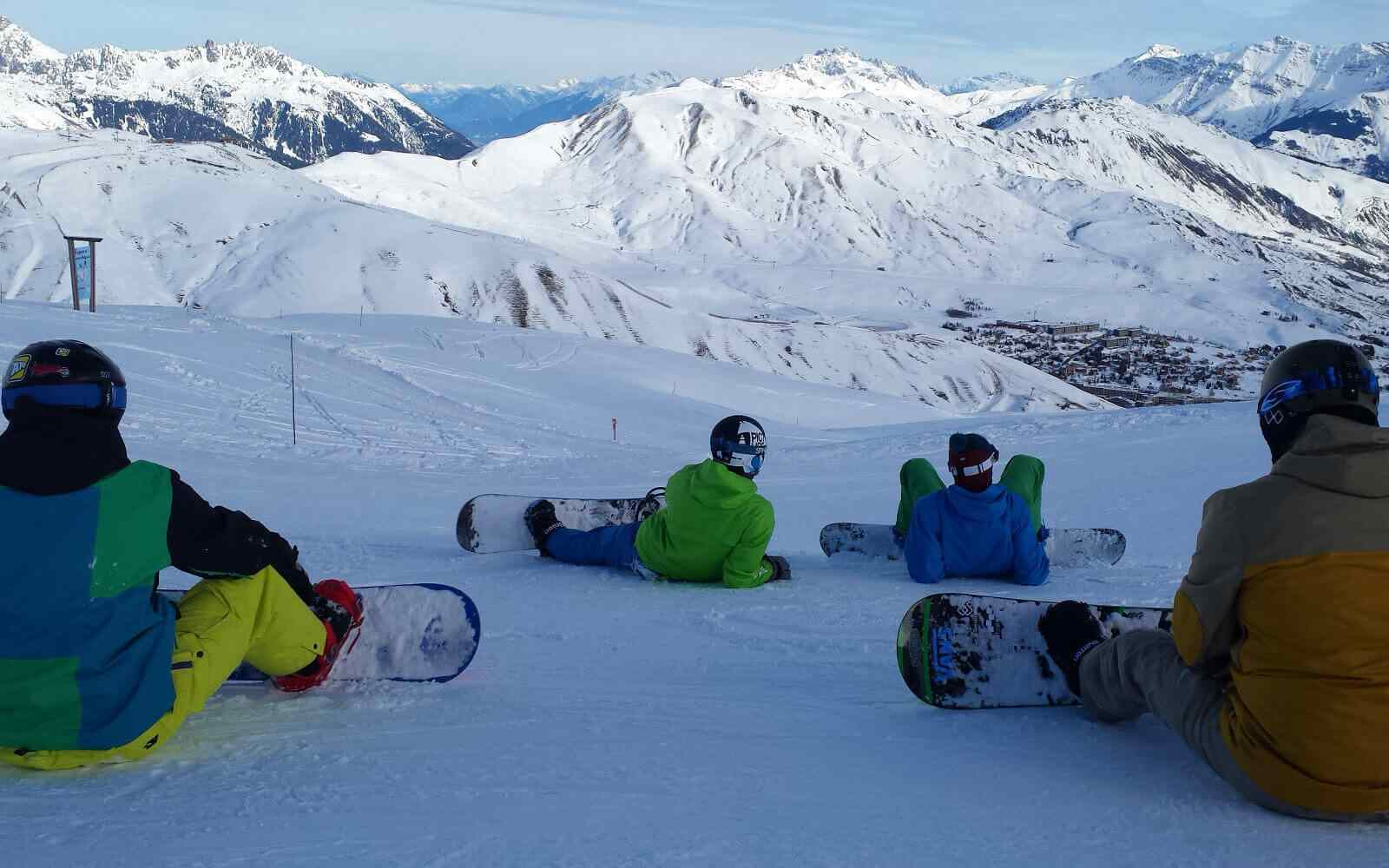 Group of snowboarders sitting down looking at mountains