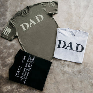 the grouping of the Dad Defined short sleeve t-shirt offerings, in grey, green, and black