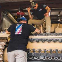 Load image into Gallery viewer, two men working on a tank while wearing the USA Matrix black short sleeve t-shirt, showcasing both the front USA logo and the back AMERICA FREEDOM transition logo