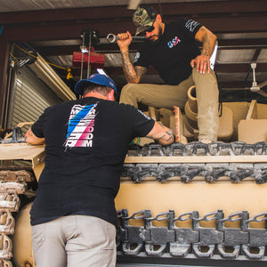 two men working on a tank while wearing the USA Matrix black short sleeve t-shirt, showcasing both the front USA logo and the back AMERICA FREEDOM transition logo