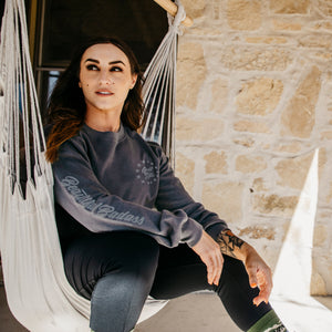 Woman sitting on a hammock and looking to the right while wearing the Women's Beautiful Badass Terry Crew Sweatshirt