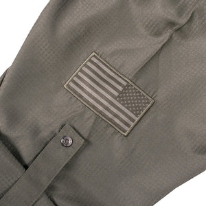 Sleeve of the Grunt Style Long Sleeve Fishing Shirt  in Olive that has the Assaulting flag logo, sleeve roll up tab, and custom buttons