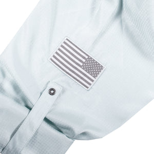 The sleeve of the Grunt Style Long Sleeve Fishing Shirt in Seafoam that has the Assaulting Flag patch and sleeve roll up tabs with custom buttons