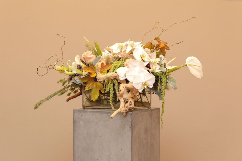 Low, long, brimful floral mix, grape-wood, curly willow & rocks