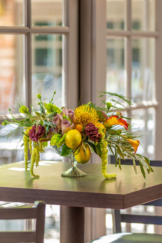 Lush mix with fruit, draping foliage, glass urn
